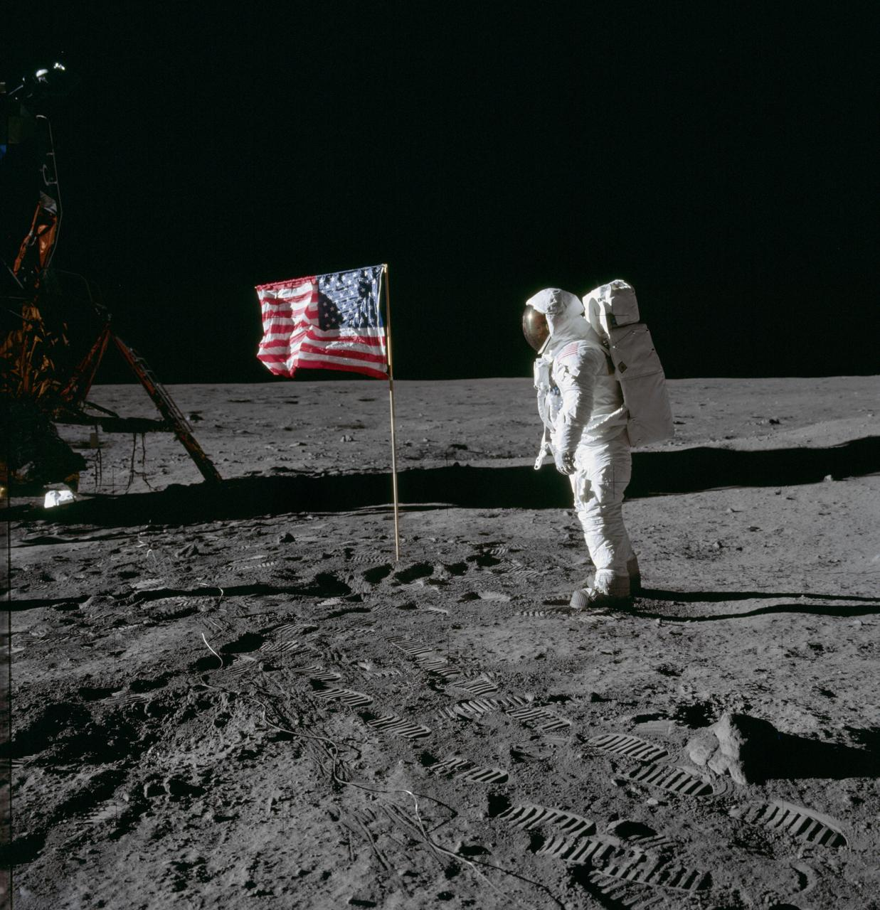 (20 July 1969) --- Astronaut Edwin E. Aldrin Jr., lunar module pilot of the first lunar landing mission, poses for a photograph beside the deployed United States flag during an Apollo 11 extravehicular activity (EVA) on the lunar surface. The Lunar Module (LM) is on the left, and the footprints of the astronauts are clearly visible in the soil of the moon. Astronaut Neil A. Armstrong, commander, took this picture with a 70mm Hasselblad lunar surface camera. While astronauts Armstrong and Aldrin descended in the LM, the